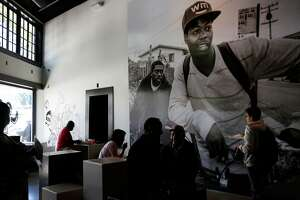 Nidamu Khuthaza, center, and Vincent Leon, right center, wait for their lunch in front of a large print by Travis Jensen in LocoL restaurant June 30, 2016 in Oakland, Calif.