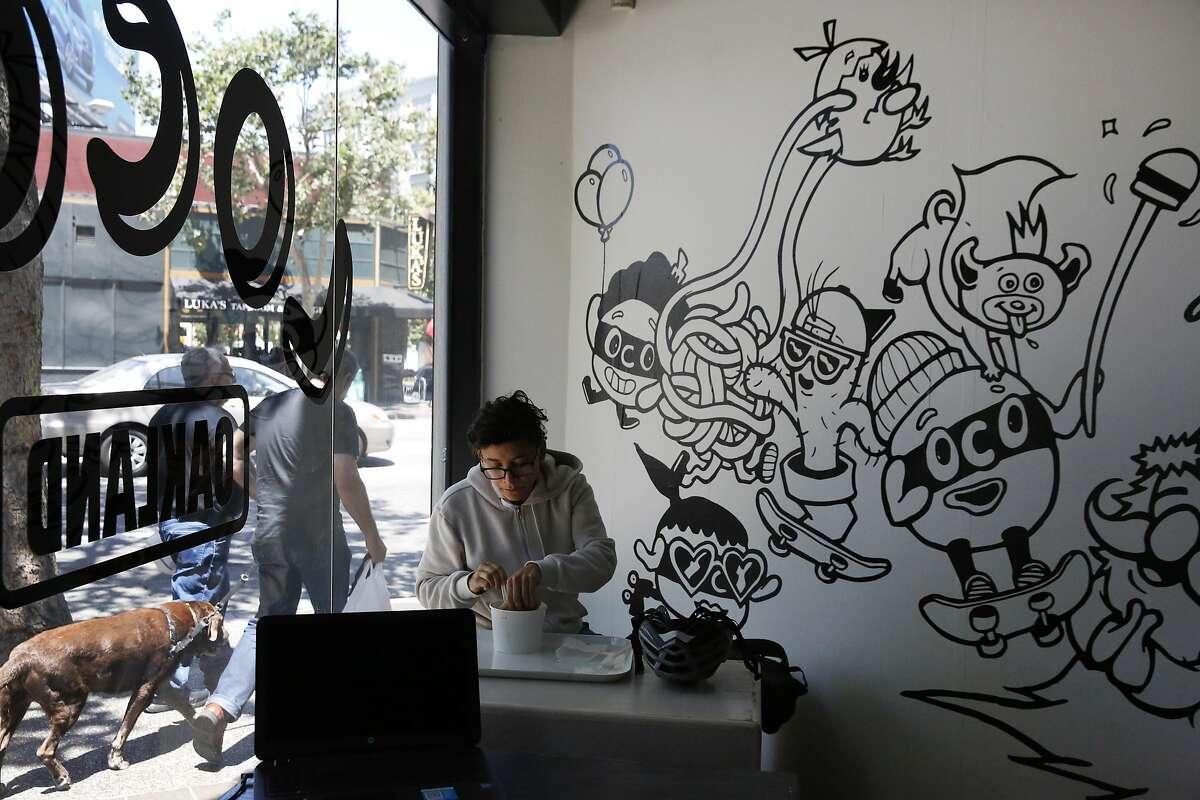 Nicole Ghan eats lunch next to artwork by Bradford Lynn in LocoL restaurant June 30, 2016 in Oakland, Calif.
