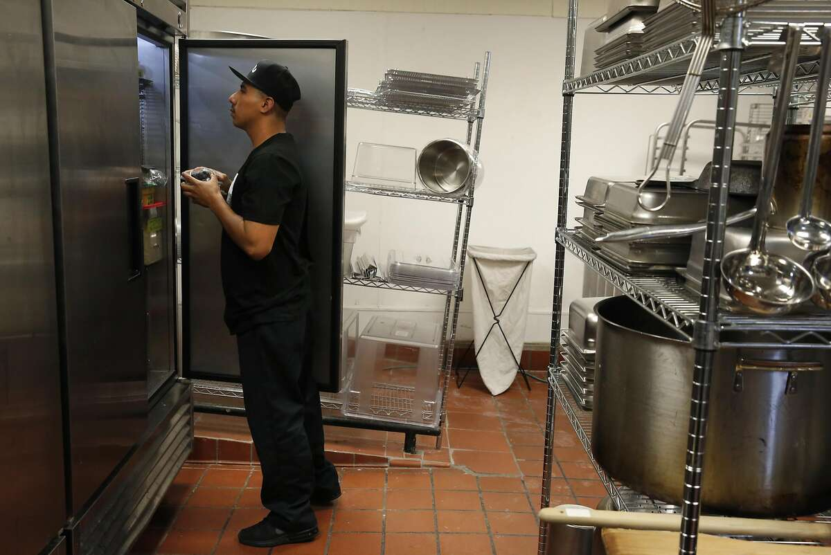 Eddie Corril removes fruit from one of the fridges in the kitchen at the commissary for LocoL restaurant June 29, 2016 in Oakland, Calif.
