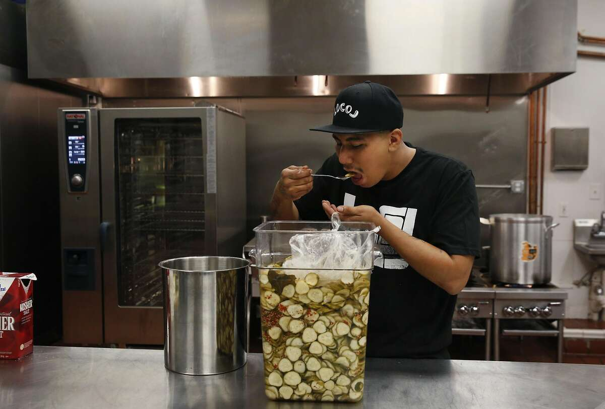 Eddie Corril takes a taste test of homemade pickles in the kitchen at the commissary for LocoL restaurant June 29, 2016 in Oakland, Calif.