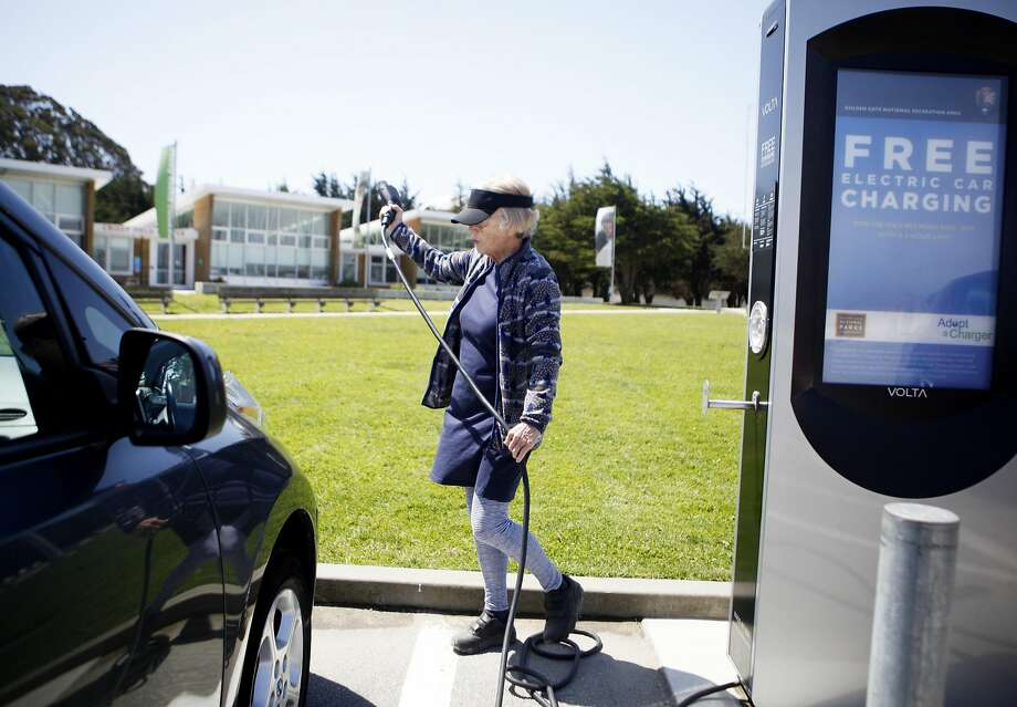Deborah Garland of San Francisco plugs in her 2014 Nissan Leaf to a charging point in San Francisco. Photo: Michael Noble Jr., The Chronicle