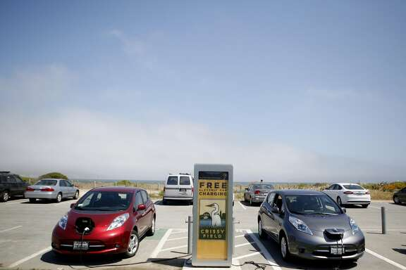 Two Nissan leafs charge at a Volta charging point on Thursday, June 30, 2016 in San Francisco, California. California is exploring changes to how it funds road repairs, currently funded by a gas tax that doesn't apply to electric-car drivers. If electric cars take off as expected, California will need to tax their driving somehow.