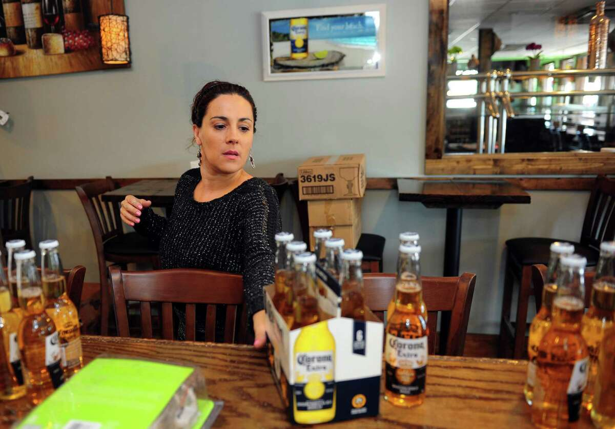 Waitress Simona Aresti stocks beer at Rancho Pantanal, a new Brazilian restaurant which opens Friday on Boston Post Road in Bridgeport, Conn., on Wednesday June 29, 2016.