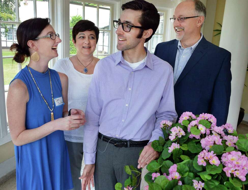 The Dupont family, from left, Jennifer,20, her mother Sue, Ernie, 24, and father Ernie share a lighter moment during a conference on a rare illness called Degos Disease pose for a photo Thursday June 30, 2016 in Saratoga Springs, NY. (John Carl D'Annibale / Times Union)