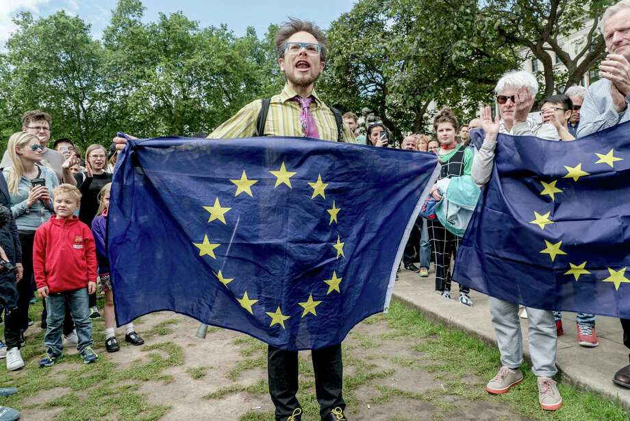 Anti-Brexit protesters hold European Union flags as they demonstrate in Parliament Square, in Westminster, central London, June 25, 2016. Britain's startling decision to pull out of the European Union set off a cascade of aftershocks on Friday, costing Prime Minister David Cameron his job, plunging the financial markets into turmoil and leaving the country's future in doubt. (Andrew Testa/The New York Times) Photo: ANDREW TESTA, STR / NYTNS