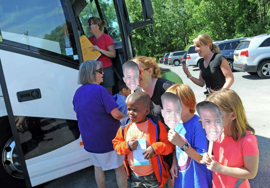 Kristi Casey of Burnt Hills and her children Delaney,7, and Keller Casey hold up masks with the face of Fresh Air participant seven-year-old Brian Nassa of the Bronx as he arrives at the Saratoga PBA range on Thursday June 30, 2016 in Saratoga Springs, N.Y. (Michael P. Farrell/Times Union) Photo: Michael P. Farrell / 40037117A