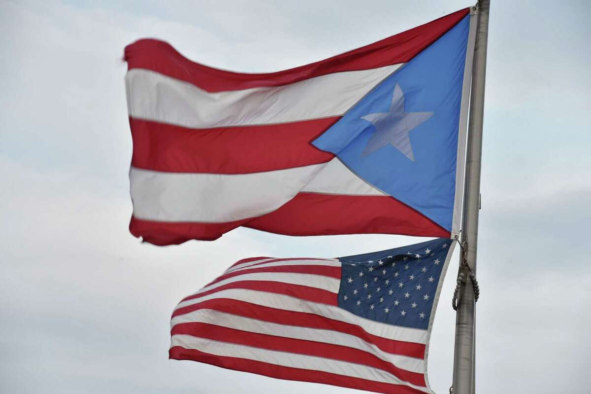(FILES) This file photo taken on February 8, 2015 shows the Puerto Rican and US flags in San Juan, Puerto Rico. The US Senate passed a bipartisan measure June 29, 2016 that would allow Puerto Rico to restructure its $70 billion debt just two days before the island was to careen into massive default. The bill, which easily passed by a vote of 68 to 30, has now cleared both chambers of Congress and will go to the White House for President Barack Obama's signature. / AFP PHOTO / Paul J. RICHARDSPAUL J. RICHARDS/AFP/Getty Images