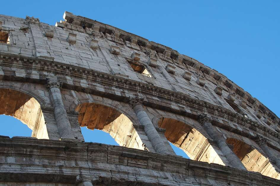 Morning light shines through the upper decks of the Colosseum in Rome.