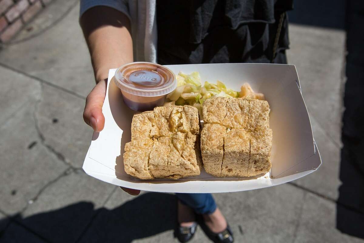 Jing Jing Qiu displays her order of Stinky Tofu from Mama Liu's food truck at the Taiwanese Night Market in Sunnyvale, Calif. on Sunday, June 26, 2016.