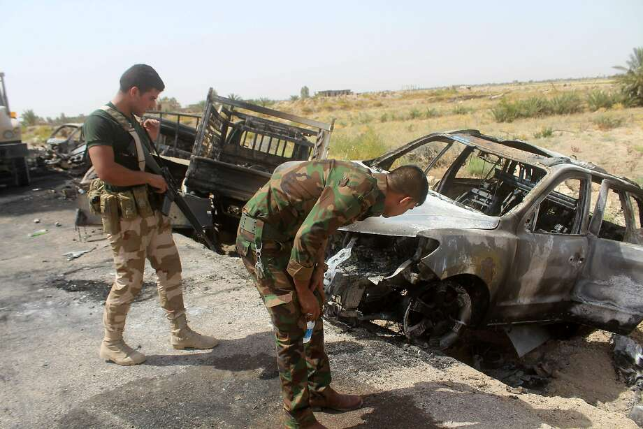 Iraqi government forces inspect charred vehicles southwest of Fallujah this week after air strikes against Islamic State fighters trying to flee the area. Photo: MOADH AL-DULAIMI, AFP/Getty Images