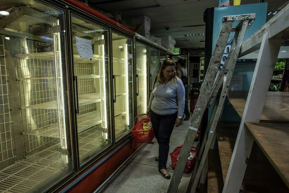 A woman passes an empty refrigerator while shopping in a grocery store in Cumana, Venezuela, June 16, 2016. The nation is anxiously searching for ways to feed itself, as the economic collapse of recent years has left it unable to produce or import sufficient food. (Meridith Kohut/The New York Times) Photo: MERIDITH KOHUT, STR / NYTNS