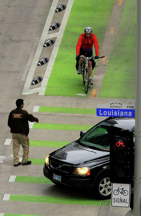 A cyclist stops for a car leaving a garage while using the bike lane on Lamar Street. Photo: Mark Mulligan, Staff / © 2015 Houston Chronicle
