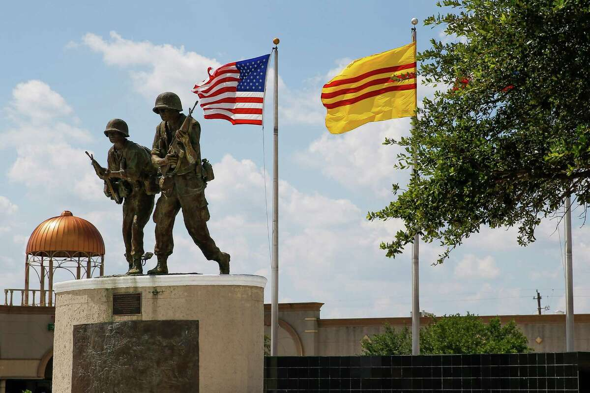 A Saigon and American flag fly above a Vietnam war memorial in the parking lot of a strip mall off Bellaire Boulevard between Turtlewood Drive and Cook Road, an area some want to call Little Saigon, on Thursday.