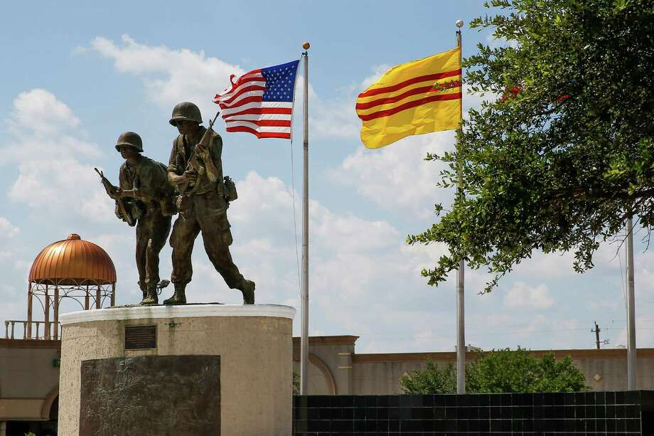 A Saigon and American flag fly above a Vietnam war memorial in the parking lot of a strip mall off Bellaire Boulevard between Turtlewood Drive and Cook Road, an area some want to call Little Saigon, on Thursday. Photo: Michael Ciaglo, Houston Chronicle / © 2016  Houston Chronicle