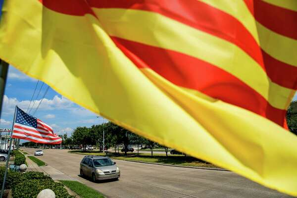 Cars drive past a Saigon flag flying alongside Bellaire Boulevard between Turtlewood Drive and Cook Road, an area some want to call Little Saigon, Thursday, June 30, 2016 in Houston.