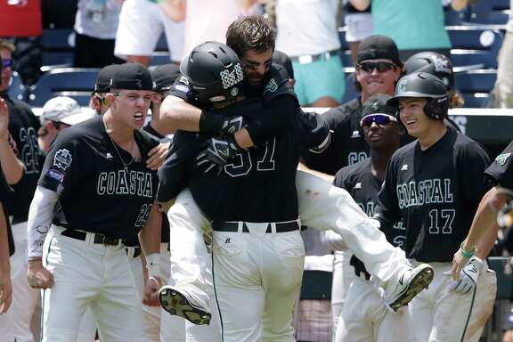 Coastal Carolina's G.K. Young (37) is hugged by Anthony Marks after hitting a two-run home run against Arizona in the sixth inning in Game 3 of the NCAA College World Series baseball finals in Omaha, Neb., Thursday, June 30, 2016. (AP Photo/Nati Harnik)