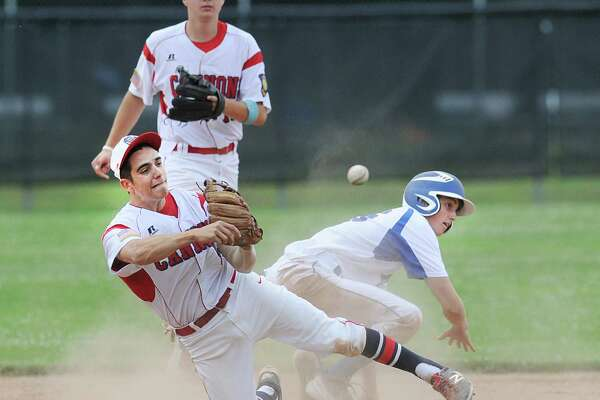 After making a diving stop and unable to get the lead Darien/New Canaan runner Ethan Ehlers at second, Greenwich second baseman Alex Loparco makes a throw from his knees in an attempt to get out a Darien/New Canaan runner who made it safely to first during the Senior Legion baseball game between Greenwich and Darien/New Canaan at Greenwich, Conn., Thursday, June 30, 2016. In the background looking on is Greenwich shortstop Colin Kelly.