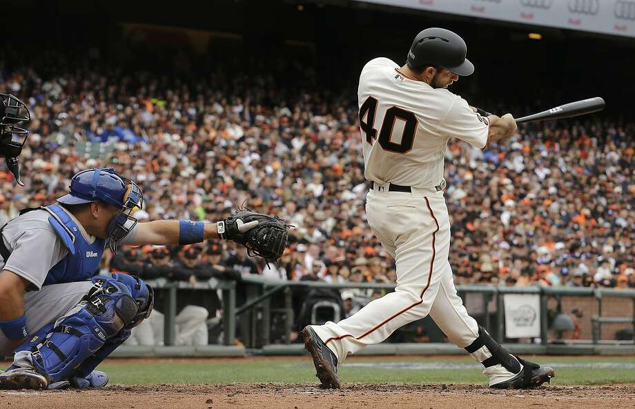 FILE - In this April 9, 2016, file photo, San Francisco Giants' Madison Bumgarner (40) hits a solo home run in front of Los Angeles Dodgers catcher A.J. Ellis during the second inning of a baseball game in San Francisco. San Francisco manager Bruce Bochy said he plans to use his slugging pitcher Bumgarner instead of a designated hitter Thursday, June 30, 2016, night when the Giants visit the Oakland Athletics. (AP Photo/Jeff Chiu, File) Photo: Jeff Chiu, Associated Press