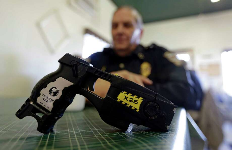 FILE - In this Nov. 14, 2013, file photo, a Taser X26 sits on a table in Knightstown, Ind. In Connecticut, a new report suggests police are more likely to use stun guns on minorities. Central Connecticut State University released its analysis Thursday, June 30, 2016, of the first statewide data of police stun gun use in the United States.  (AP Photo/Michael Conroy, File) Photo: Michael Conroy, STF / AP2013