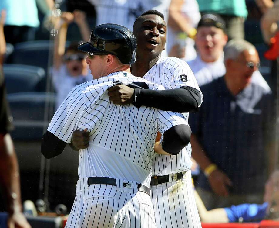 NEW YORK, NY - JUNE 30:  Chase Headley #12 of the New York Yankees is congratulated by teammate Didi Gregorius #18 after Headley scores on a passed ball in the ninth inning against the Texas Rangers at Yankee Stadium on June 30, 2016 in the Bronx borough of New York City. The New York Yankees defeated the Texas Rangers 2-1.  (Photo by Elsa/Getty Images) ORG XMIT: 607680785 Photo: Elsa / 2016 Getty Images
