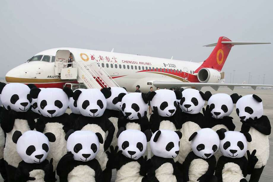 People in panda outfits pose by a Chengdu Airlines ARJ21-700 plane before its first commercial flight. Photo: Ding Ting, SUB / Xinhua