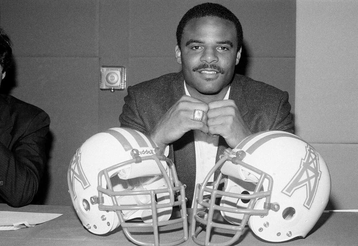 University of Washington quarterback Warren Moon poses with Houston Oilers helmets during a press conference in Los Angeles at which it was announced the Canadian Football League standout had signed with the Oilers for the upcoming season, Feb. 7, 1984. The Oilers beat out Seattle for the free agent.