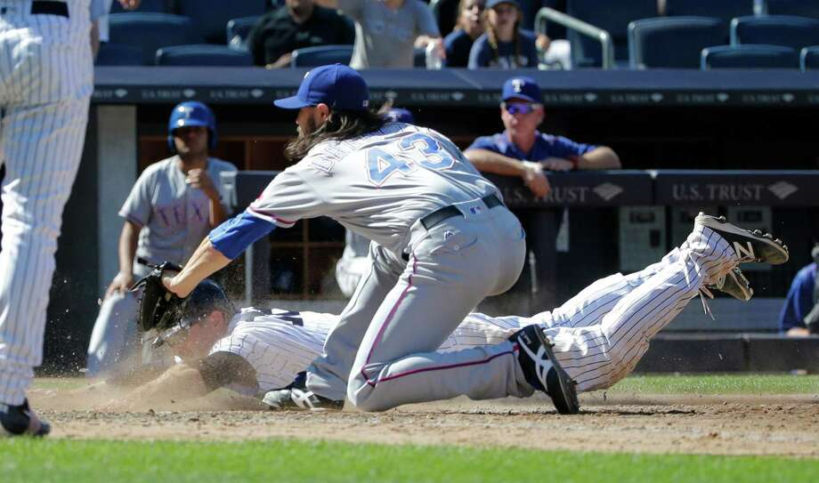 The Yankees' Chase Headley, left, slides past Rangers pitcher Tony Barnette to score the winning run on a passed ball in the ninth inning. Photo: Frank Franklin II, STF / Copyright 2016 The Associated Press. All rights reserved. This material may not be published, broadcast, rewritten or redistribu
