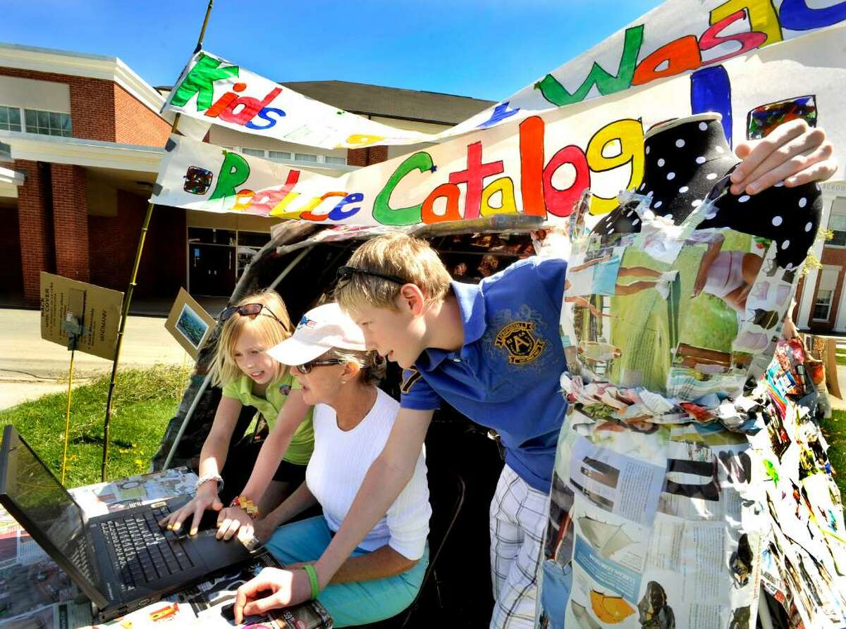 Anna Harrison, 10, left, and Adam Harrison, 13, right, register Claudia Coopersmith at kidsagainstwaste.com to reduce unwanted catalogues during the third annual Newtown Earth Day Festival. All three are of Newtown.