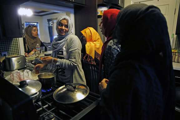 (left to right) Yasmeen Hakim, Amina Hakim, Shukria Hakim, Hanan Mubarez, 14, Ruqaya Mubarez, 13, congregate in the kitchen as they prepare food before breaking their Ramadan fast in San Leandro, Calif., on Thursday, June 30, 2016.