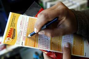 Sara Thompson picks numbers for her Mega Millions lottery ticket at a convenience store in Chicago, Friday, July 1, 2016. Friday night's Mega Millions drawing will give lottery players a shot at the 10th largest jackpot in U.S. history. (AP Photo/Nam Y. Huh)