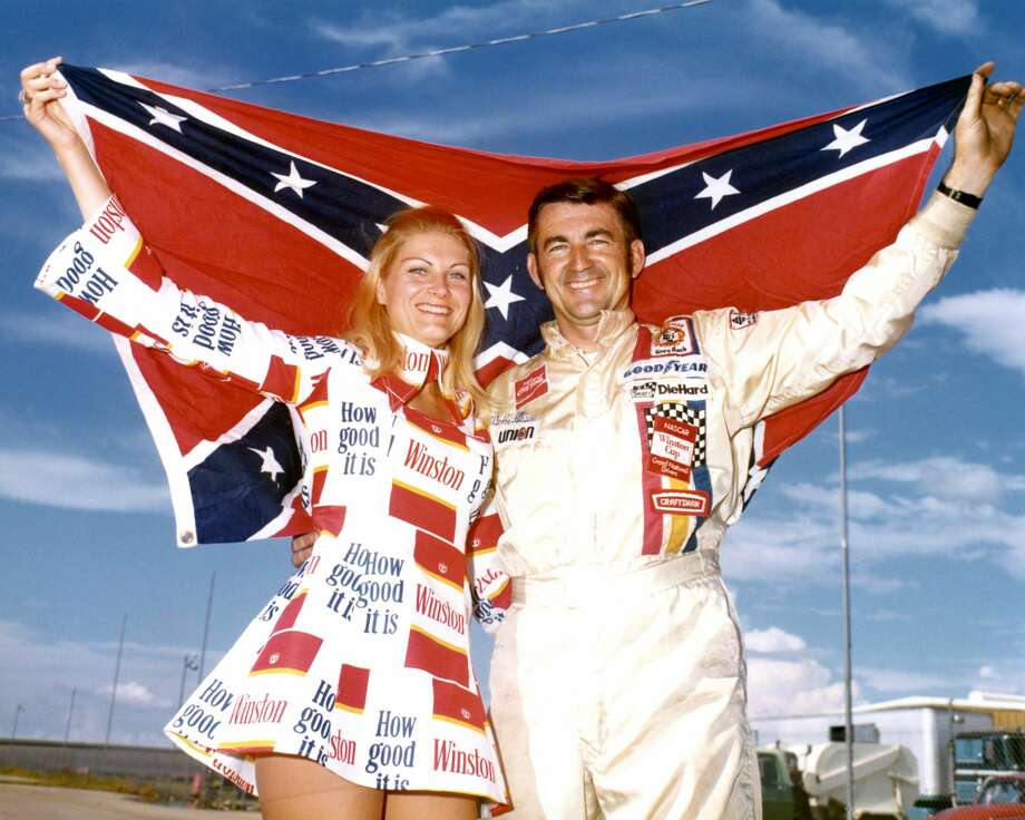 Then: In 1973, Driver Bobby Allison holds up a confederate flag with Miss Winston, Noneen Hulbert, before the Alamo 500 race at the Texas World Speedway in College Station. Photo: Dozier Mobley/Getty Images, Getty Images