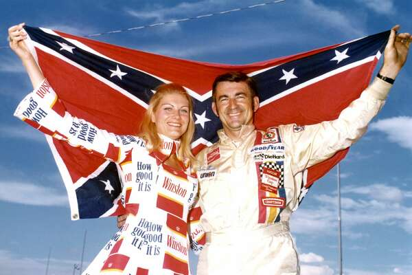 1973: COLLEGE STATION, TX - JUNE 10: Driver Bobby Allison holds up a confederate flag with Miss Winston, Noneen Hulbert, before the Alamo 500 race at the Texas World Speedway in College Station, Texas. (Photo by Dozier Mobley/Getty Images)