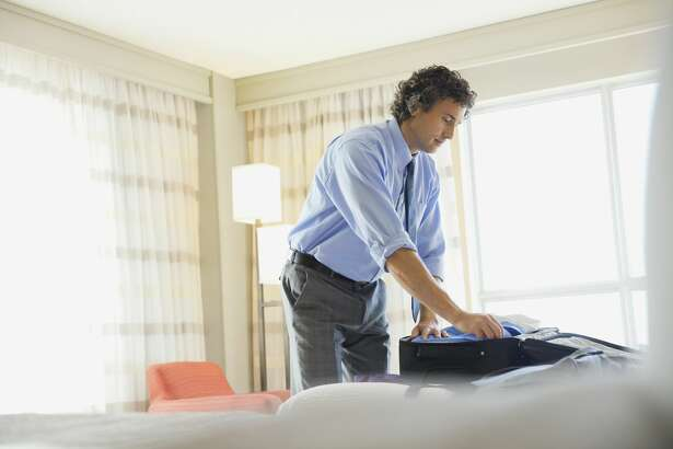 Businessman packing suitcase in hotel room