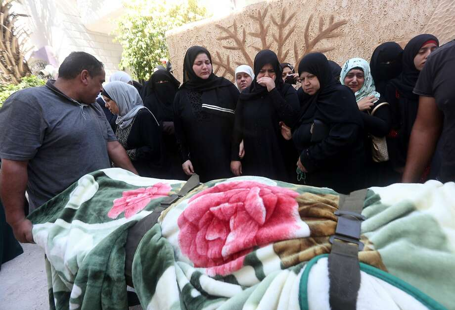 Mourners stand next to the body of Sondos al-Basha, a Palestinian woman who was killed in the Istanbul airport attack blamed on the Islamic State (IS) group on June 28, during her funeral in the West Bank town of Qalqilyah on July 1, 2016. The suicide attackers who launched the deadly Istanbul airport assault were planning to take dozens of passengers hostage, Turkish media reported on July 1, 2016, as CCTV of the bombers' faces emerged. Turkish officials have pointed blame at the Islamic State jihadist group for the gun and bomb spree at Ataturk airport, which left at least 44 people dead including 19 foreigners. / AFP PHOTO / JAAFAR ASHTIYEHJAAFAR ASHTIYEH/AFP/Getty Images Photo: JAAFAR ASHTIYEH, AFP/Getty Images