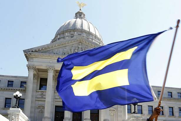 The Human Rights Campaign's flag, the largest national lesbian, gay, bisexual, transgender and queer civil rights organization, is waved on the steps of the Mississippi Capitol in Jackson, Miss., Friday, July 1 2016. Activists celebrated Thursday's ruling of a federal judge who blocked a Mississippi law on religious objections to same-sex marriage moments before it was set to take effect Friday, ruling it unconstitutionally establishes preferred beliefs and creates unequal treatment for gay people. (AP Photo/Rogelio V. Solis)