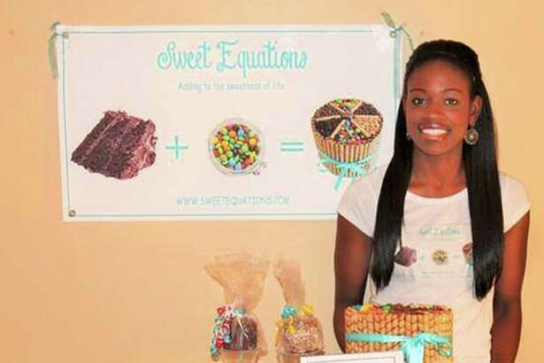 Sade Owoye of Danbury, owner of Sweet Equations bakery, stands next to some of her products at a recent event.