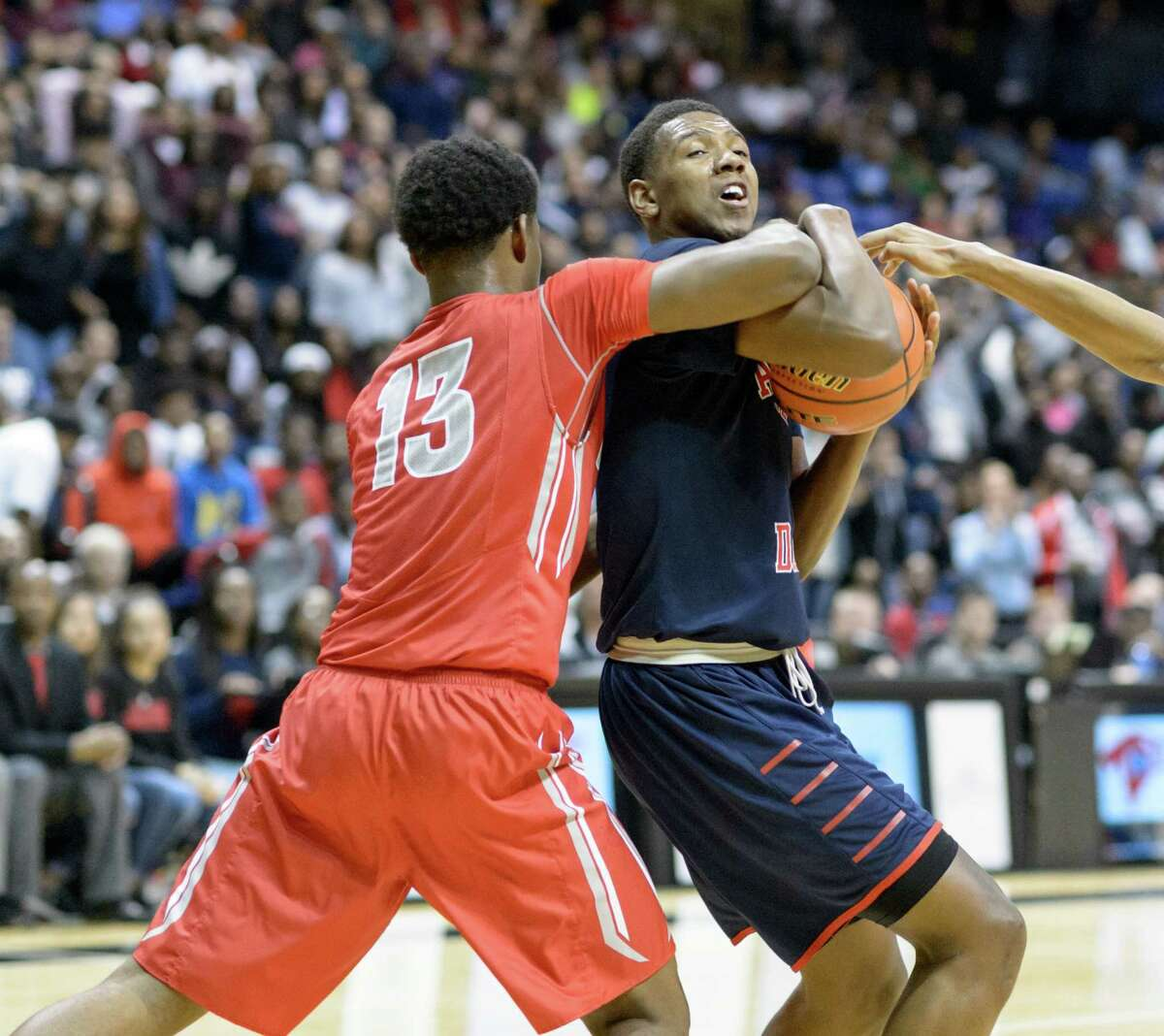 Royce Hamm (1) of the Davis Falcons battles Jared Garcia (13) of the Cy Lakes Spartans for the ball in the first half in high school basketball's Class 6A Regional Quarterfinals on Tuesday, March 1, 2016 at the Berry Center.