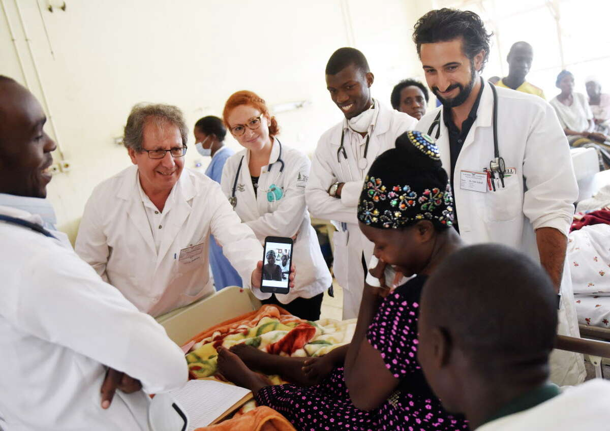 Danbury Hospital Global Health Department Director Dr. Majid Sadigh, second from left, takes a photo of a patient and shows it to her during clinical rounds with other medical students and residents at Mulago Hospital in the capital city of Kampala, Uganda Friday, July 24, 2015.
