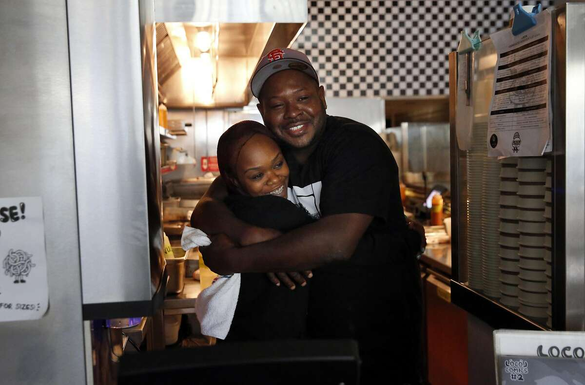 Keith Corbin, Director of Operations, gives General Manager Devignai Carroll a birthday hug as she waits at the cash register for the next customer in LocoL restaurant June 29, 2016 in Oakland, Calif.