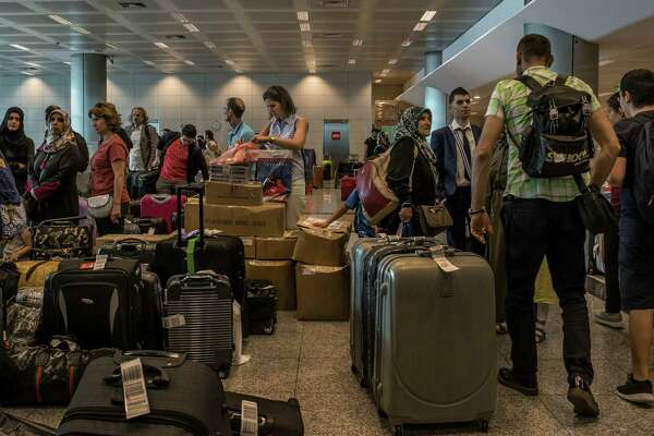Passengers wait for their luggage at a busy belt after arriving at the partially damaged international terminal at the Ataturk Airport in Istanbul. Hours after the suicide attack that killed 41 and wounded more than 200, the airport resumed limited flights as workers continued repairs.