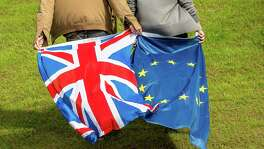 People display United Kingdom and Europe's flags. Turmoil gripped Britain's main political parties after the shock vote to leave the EU, and the repercussions were felt around the world.