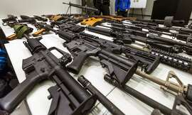 FILE - In this Dec. 27, 2012, file photo, a variety of military-style semi-automatic rifles obtained during a buy back program are displayed at Los Angeles police headquarters. Gov. Jerry Brown signed six stringent gun-control measures Friday, July 1, 2016, that will require people to turn in high-capacity magazines and require background checks for ammunition sales, as California Democrats seek to strengthen gun laws that are already among the strictest in the nation. (AP Photo/Damian Dovarganes, File)