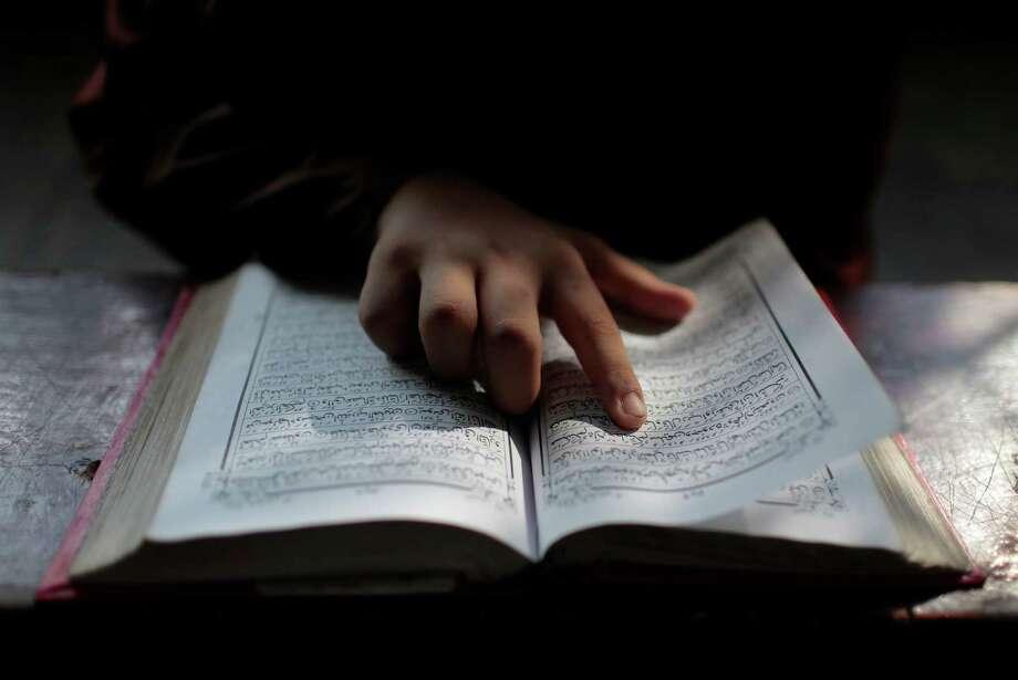 A Bangladeshi Muslim student reads the holy Quran at an Islamic school during Ramadan in Dhaka, Bangladesh. Muslims throughout the world are marking the holy month of Ramadan, during which they fast from dawn till dusk. Photo: A.M. Ahad, STR / AP