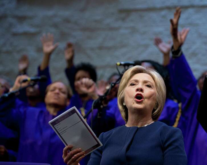 FILE - In this March 13, 2016, file photo, Democratic presidential candidate Hillary Clinton sings during service at Mount Zion Fellowship Church in Highland Hills, Ohio. Black Baptist churches may not seem like an obvious match for Clinton, a white Methodist from the Chicago suburbs. But the Democratic presidential candidate, who has been criticized for her tentative or even awkward political skills, often seems most at ease in these churches where she has shared her faith for many years and earned a loyal following in the process. (AP Photo/Carolyn Kaster, File)
