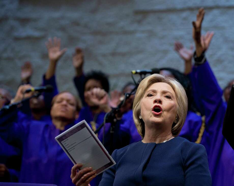 FILE - In this March 13, 2016, file photo, Democratic presidential candidate Hillary Clinton sings during service at Mount Zion Fellowship Church in Highland Hills, Ohio. Black Baptist churches may not seem like an obvious match for Clinton, a white Methodist from the Chicago suburbs. But the Democratic presidential candidate, who has been criticized for her tentative or even awkward political skills, often seems most at ease in these churches where she has shared her faith for many years and earned a loyal following in the process. (AP Photo/Carolyn Kaster, File) Photo: Carolyn Kaster, STF / Copyright 2016 The Associated Press. All rights reserved. This material may not be published, broadcast, rewritten or redistribu