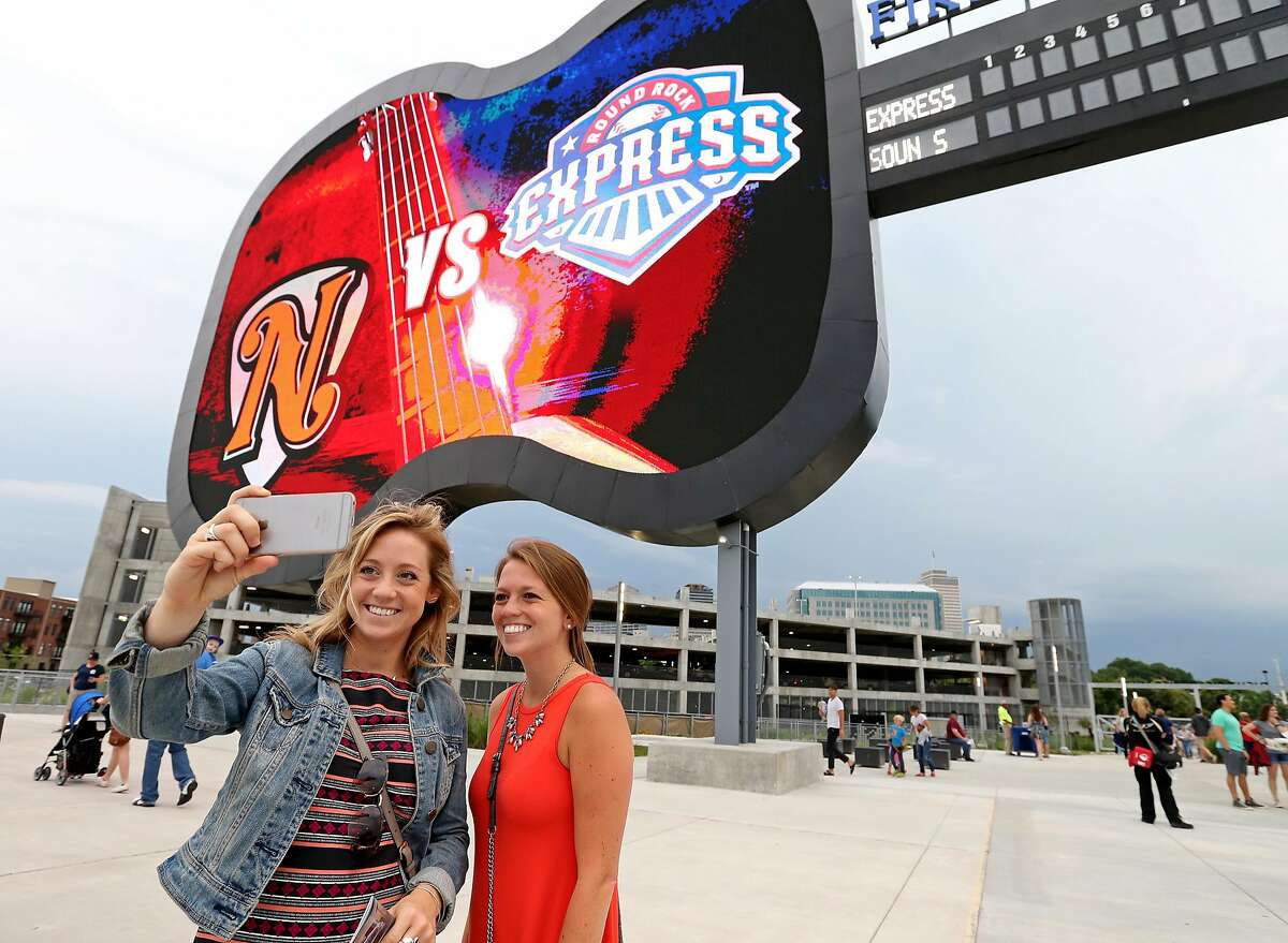 Sisters Lynn (left) and Angela Lazzeretti take a selfie with the scoreboard at First Tennessee Park before the Nashville Sounds and Round Rock Express baseball game Friday June 3, 2016 in Nashville, Tennessee.