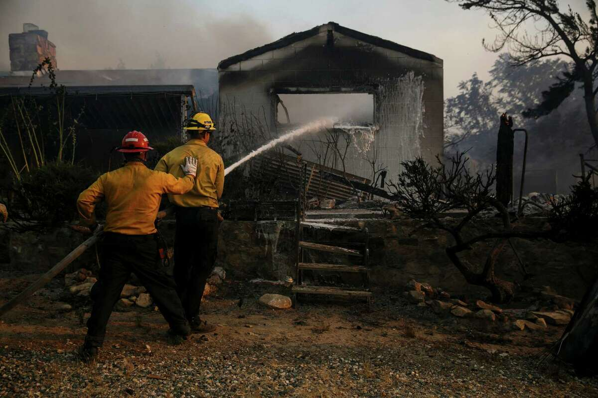 Fire crews extinguish flames at a smoldering home last month along South Kelso Valley Road in Weldon, an unincorporated area in Kern County.