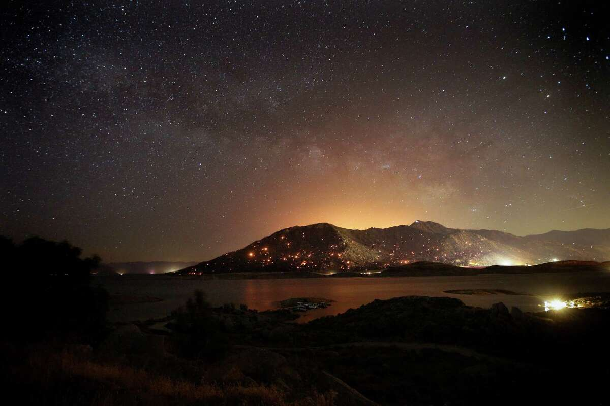 Embers burn on the mountain as firefighters continue to battle a wildfire in the area Friday, June 24, 2016, near Lake Isabella, Calif. The vast and voracious wildfire that has burned at least 80 homes in central California killed an elderly couple as they tried to flee, authorities said. (AP Photo/Jae C. Hong)