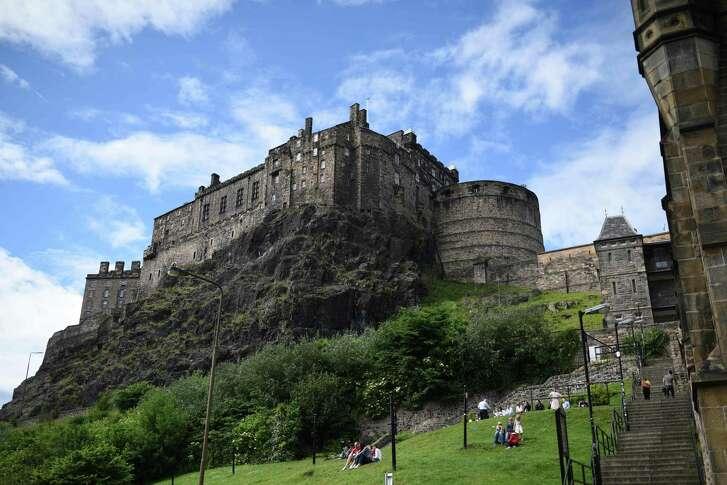 Members of the public relax in small park beneath Edinburgh castle in Edinburgh, Scotland.