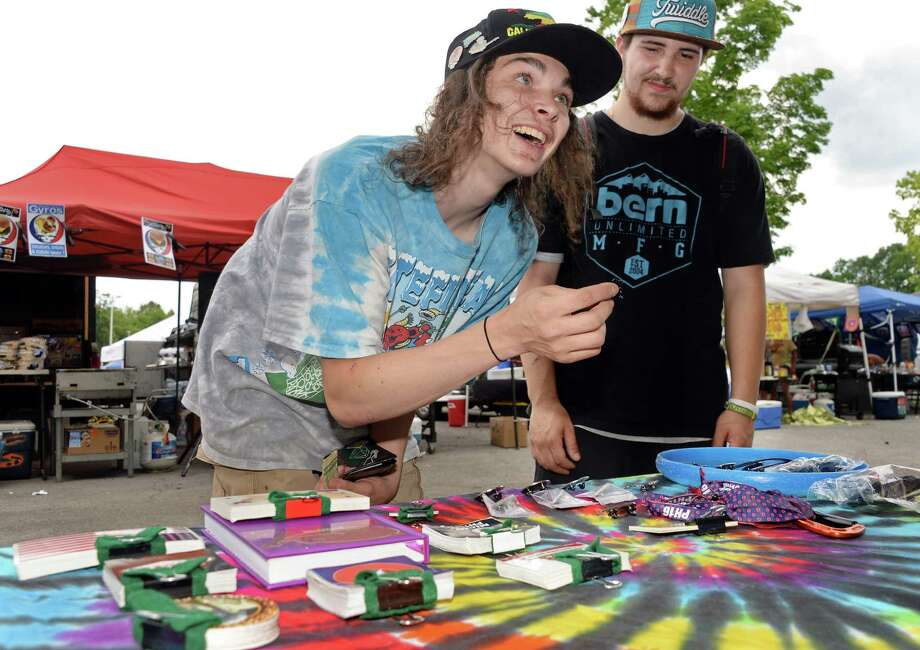 Nick Loveland, left, and Alejandro Rantanen of Rutland, VT, check out souvenir  pins and stickers before tonight's Phish concert at SPAC Friday July 1, 2016 in Saratoga Springs, NY.  (John Carl D'Annibale / Times Union) Photo: John Carl D'Annibale / 40036878A